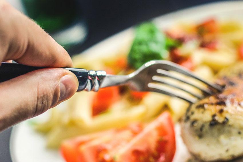 Persona pinchando comida con el tenedor