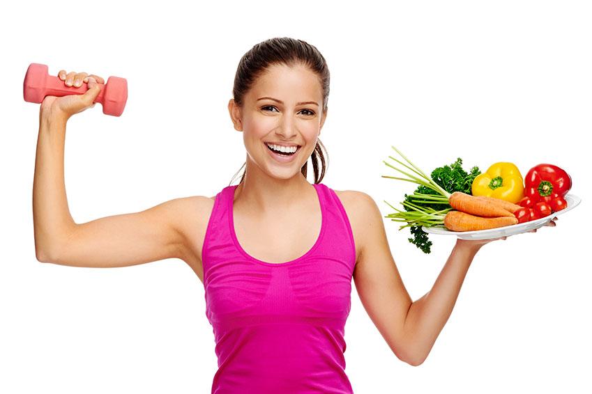 Mujer sosteniendo una bandeja de fruta y verdura mientras hace ejercicio